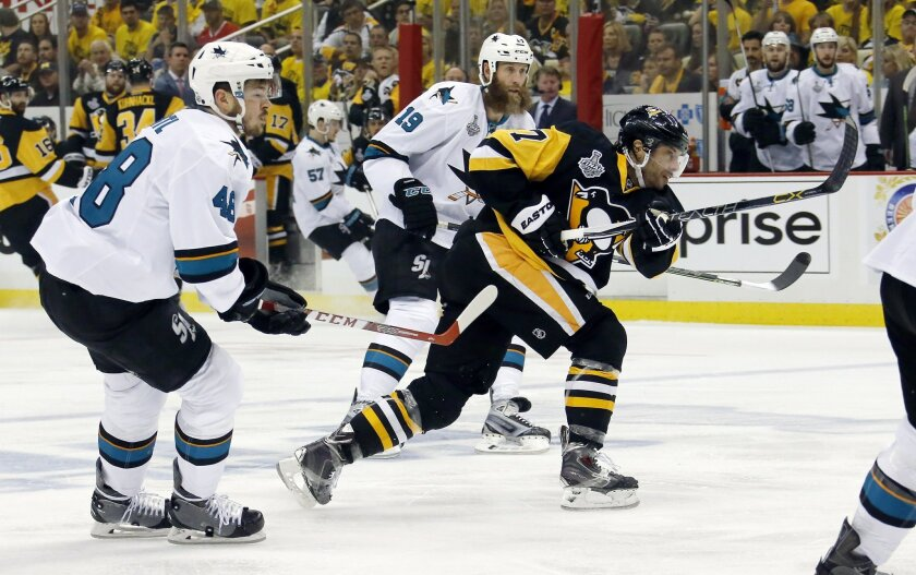 Pittsburgh Penguins' Sidney Crosby (87) follows through on a shot in front of San Jose Sharks' Tomas Hertl (48) and Joe Thornton (19) during the first period in Game 2 of the NHL hockey Stanley Cup Finals on Wednesday, June 1, 2016, in Pittsburgh. (AP Photo/Keith Srakocic)