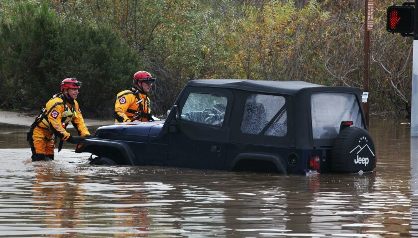 San Diego, CA. January 6, 2016 |  San Diego Lifeguards, members of the swift water rescue team, push a jeep with the driver, Cynthia Carrillo, out of deep water at the intersection of Mission Center Road and Hazard Center Dr. Thursday morning. Carrillo thought she could make it across.  Alpha Proje