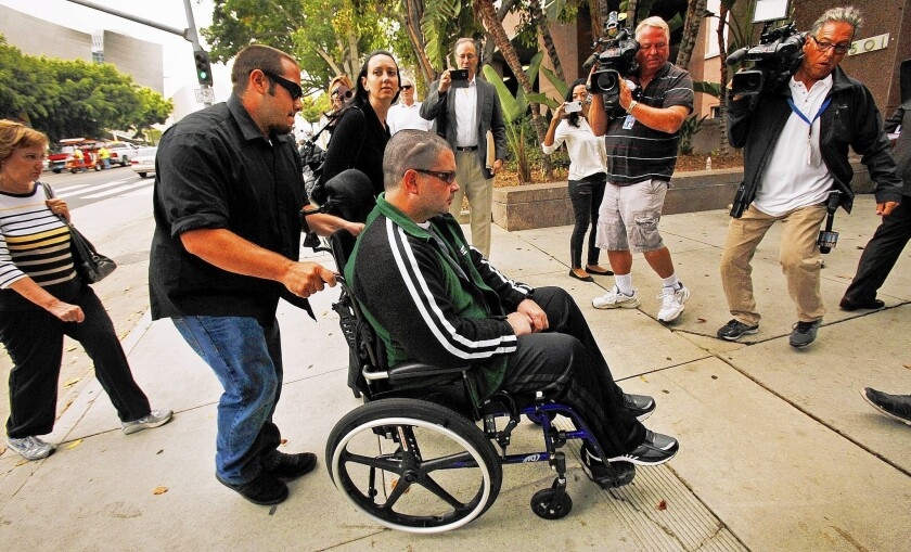 A wheelchair-bound Bryan Stow is surrounded by his mother, sister and media as he is led into the courthouse in downtown L.A. on Wednesday.