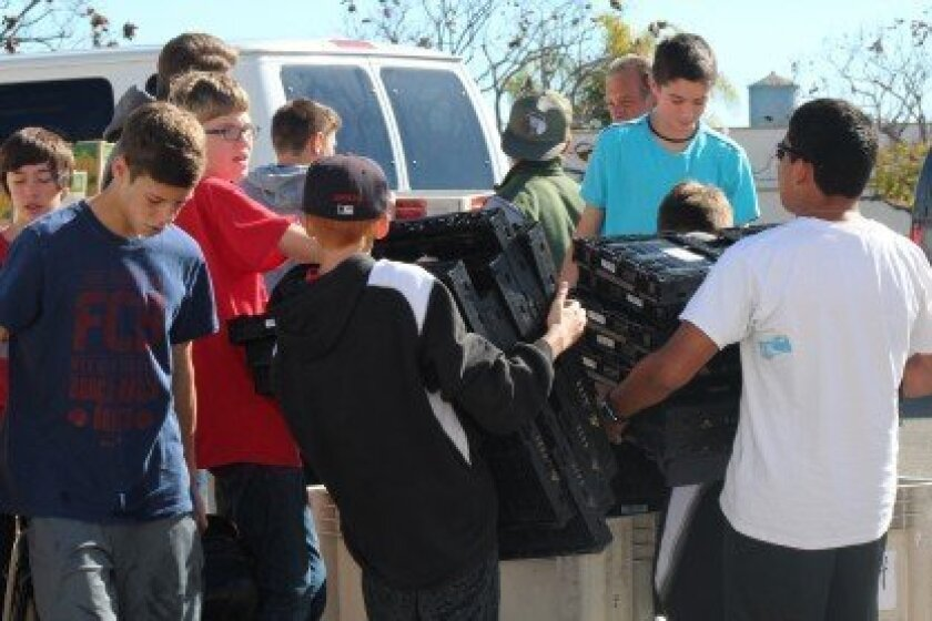 Santa Fe Christian Middle School students Bryson Shores, Tony Perez, Austinn Rossetti, TJ Askew and George Devries clean and organize bins for food distribution.