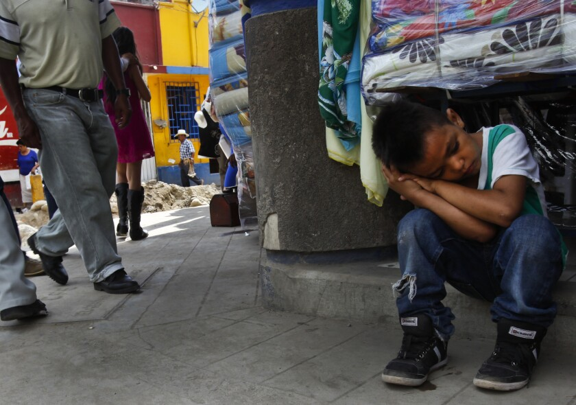 Anderson Daniel, 7, from Honduras, sits exhausted on a hot street in the southern Mexican city of Tapachula. Migrants, including minors, pass through on their way to the United States. Many never make it and are either deported or end up staying on in Mexico's poorest state.