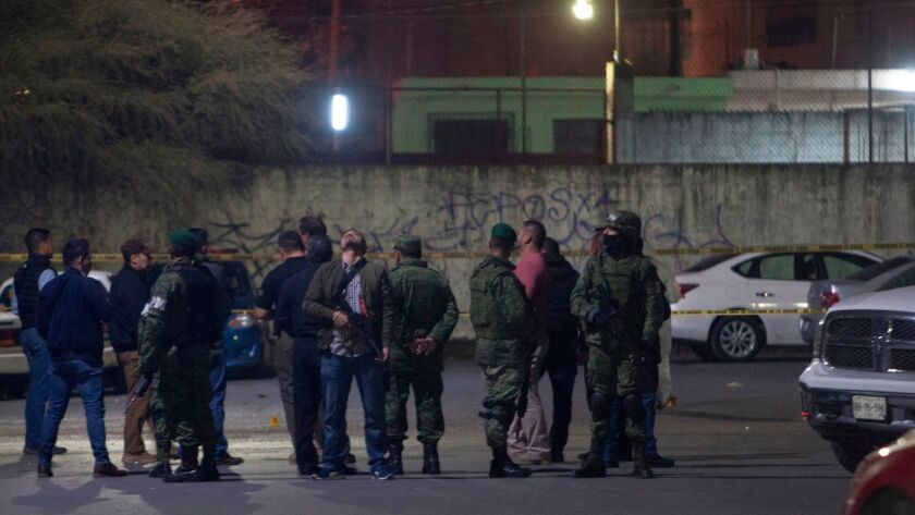 Members of the Mexican army on Sunday monitor the area where nine people were killed inside a house while watching a soccer game near Monterrey, Mexico.