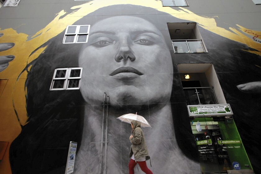 """A pedestrian makes her way through the rain past the mural """"Our Lady of DTLA"""" on the SB Tower building on Spring Street."""