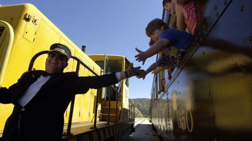 Campo Railroad Museum train conductor Seth Miller reaches for the hands of the children as they wait for the train to leave Campo Depot.