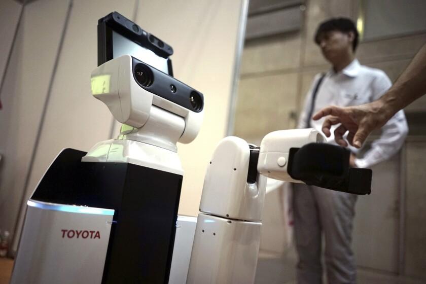 El nuevo robot HSR de Toyota en una muestra sobre enfermería y atención sanitaria en Yokohama, al sur de Tokio. El nuevo robot se desliza como R2-D2 y se centra en una tarea sencilla: recoger cosas.