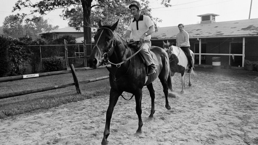 Seattle Slew, with exercise boy Mike Kennedy, returns to his Pimlico barn on May 20, 1977, after his
