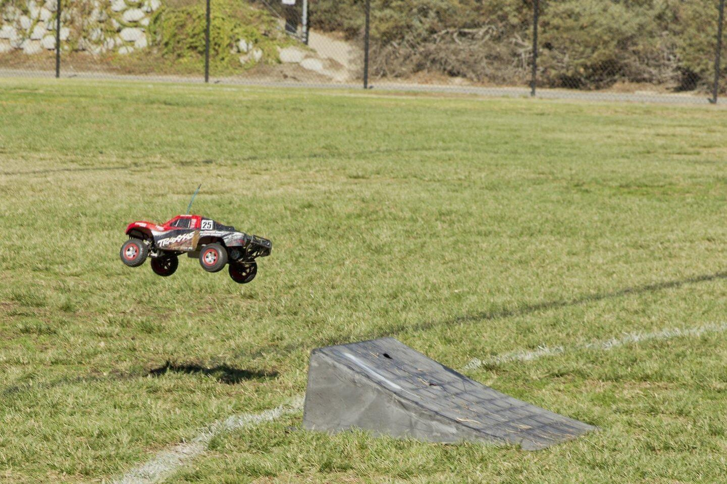 Radio-controlled cars jump off the ramp at the Drones, Donuts, and Dads event at Carmel Creek School