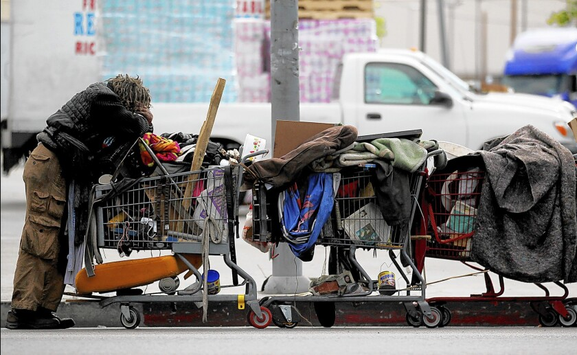 A man pulling a line of shopping carts pauses along Ninth Street in downtown Los Angeles.
