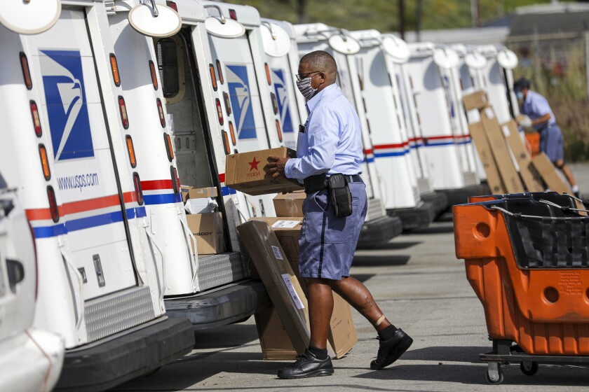 Postal carrier James Daniels loads mail in his truck for delivery at the San Clemente Post Office on May 15.