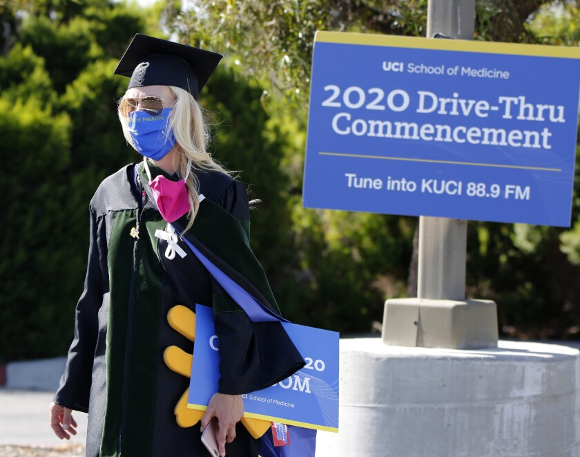 "A UC Irvine administrator wearing cap, gown and mask walks past a sign announcing a ""drive-through commencement"""