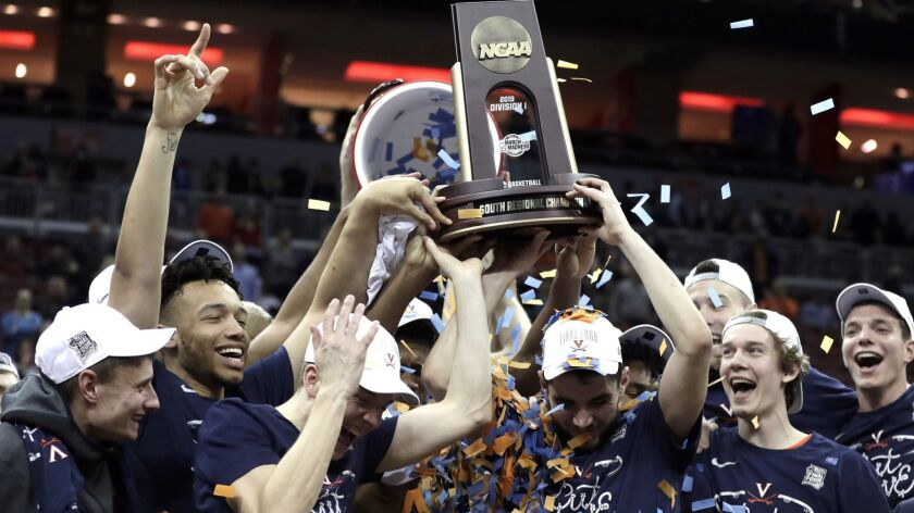 Members of Virginia celebrate after defeating Purdue 80-75 in overtime of the men's NCAA Tournament