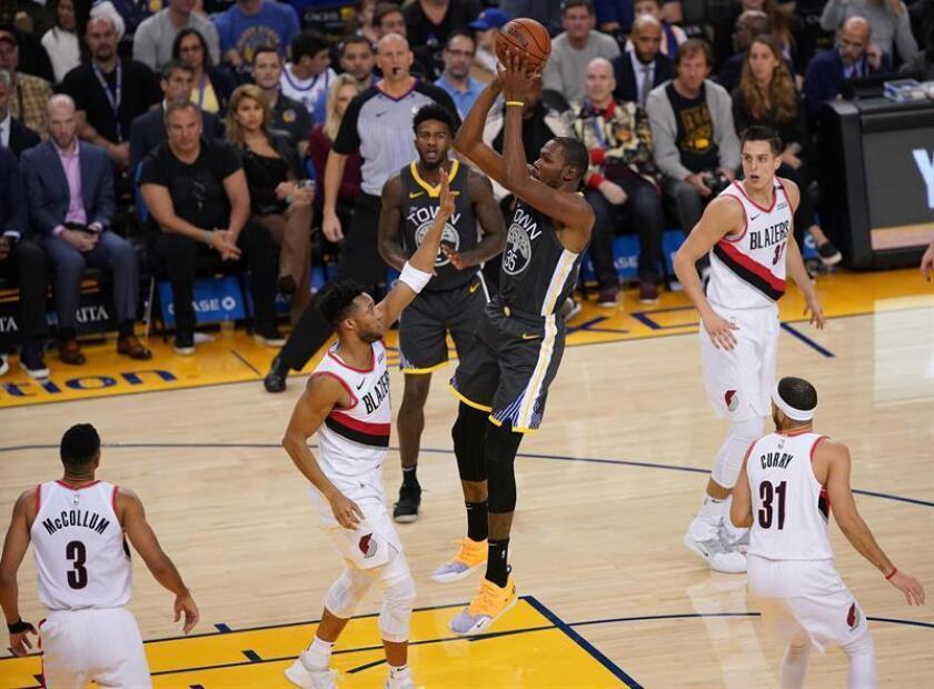 El alero de los Golden State Warriors Kevin Durant (c) intenta encestar hoy durante el partido disputado contra los Portland Trail Blazers en el Oracle Arena de Oakland, California. EFE