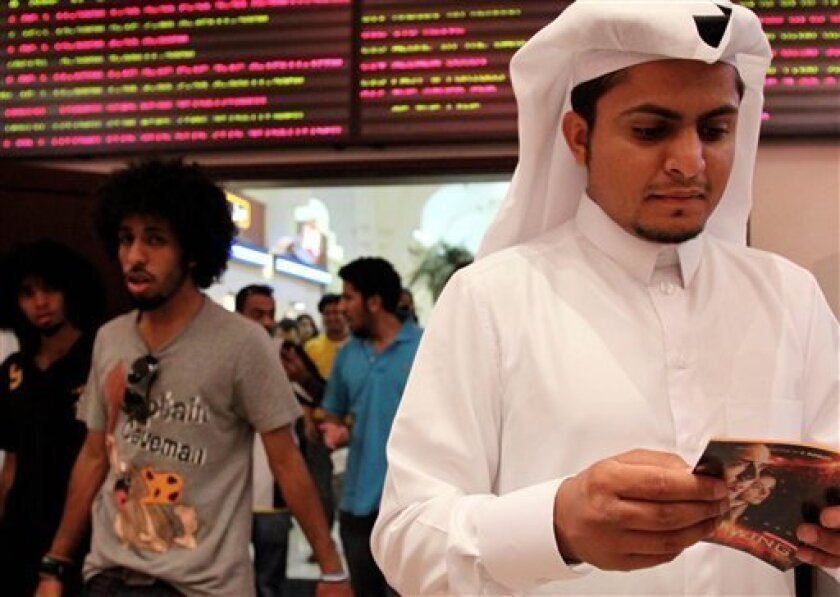 In this photo taken on May 7, 2009, Walid al-Musharraf, 27, of Riyadh, Saudi Arabia, looks at a brochure outside a Manama, Bahrain, movie theater. Al-Musharraf says he likes to watch foreign films and sees no reason his country should not have cinemas, noting that movies can be educational. Bahrain