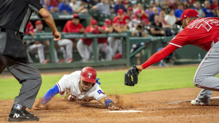 Texas Rangers' Robinson Chirinos scores ahead of the tag of pitcher Osmer Morales (73) on a wild pitch by Morales during the eighth inning.
