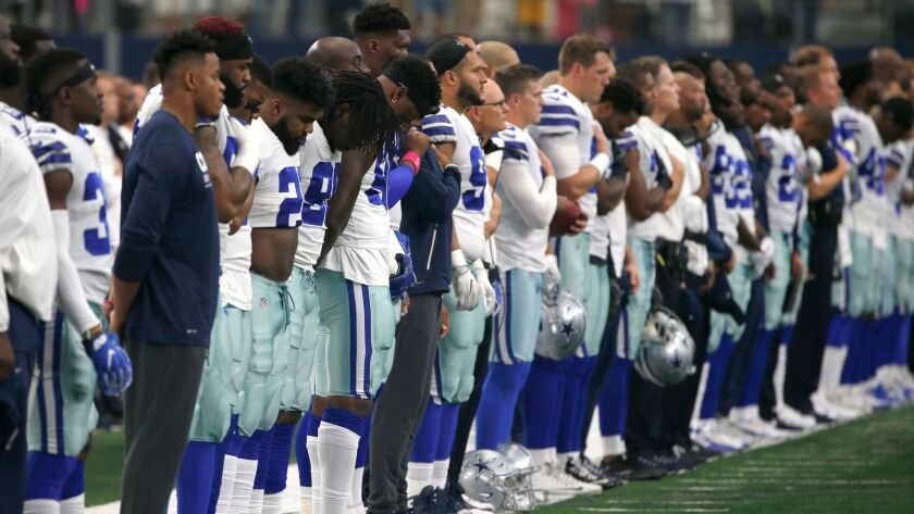 The Dallas Cowboys and staff stand on the sideline during the playing of the national anthem before