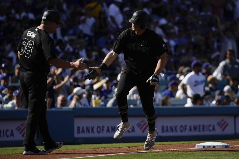 Yankees first baseman DJ LeMahieu is congratulated by third base coach Phil Nevin after hitting a home run.