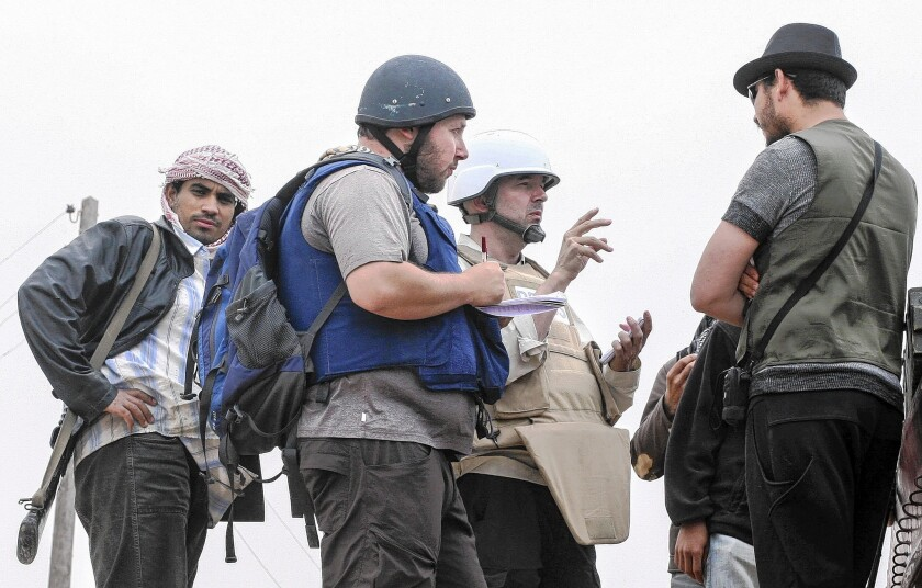 American journalist Steven Sotloff, center with black helmet, talks to Libyan rebels near Misurata in June 2011. Islamic State rebels who took him hostage have threatened to kill him.