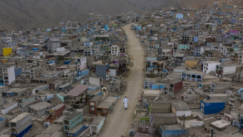 """Brother Ronald Marin, a 30-year-old layworker from Venezuela, walks along a paved dirt road lined by graves, inside the """"Martires 19 de Julio"""" cemetery in Comas, on the outskirts of Lima, Peru, Saturday, July 4, 2020. Wearing a white robe and shoes worn down by dust, Marin is one of the few who administers funerals in this cemetery far from the center of Peru's capital. (AP Photo/Rodrigo Abd)"""