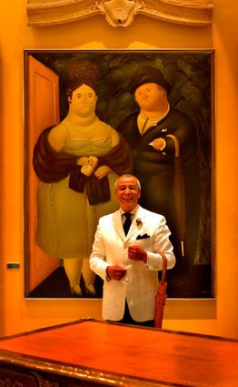 """Bijan Pakzad smiles in his Rodeo Drive boutique. Behind him is a painting by Fernando Botero called """"The Rich."""" Pakzad, who was born in Iran and dressed presidents and celebrities, once boasted in an ad that he sold """"the costliest menswear in the world."""""""