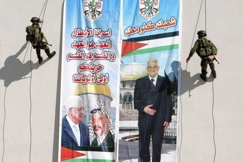 Palestinian security officers in Jenin, West Bank, make their way down a building adorned with a banner bearing images of Palestinian Authority leader Mahmoud Abbas, left, and his late predecessor, Yasser Arafat.