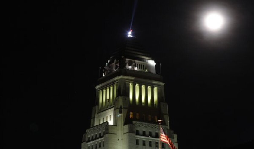 One kind of blue moon, the second in one calendar month, rises over Los Angeles City Hall on Dec. 31, 2009. A different kind of blue moon will shine above the Southland tonight.