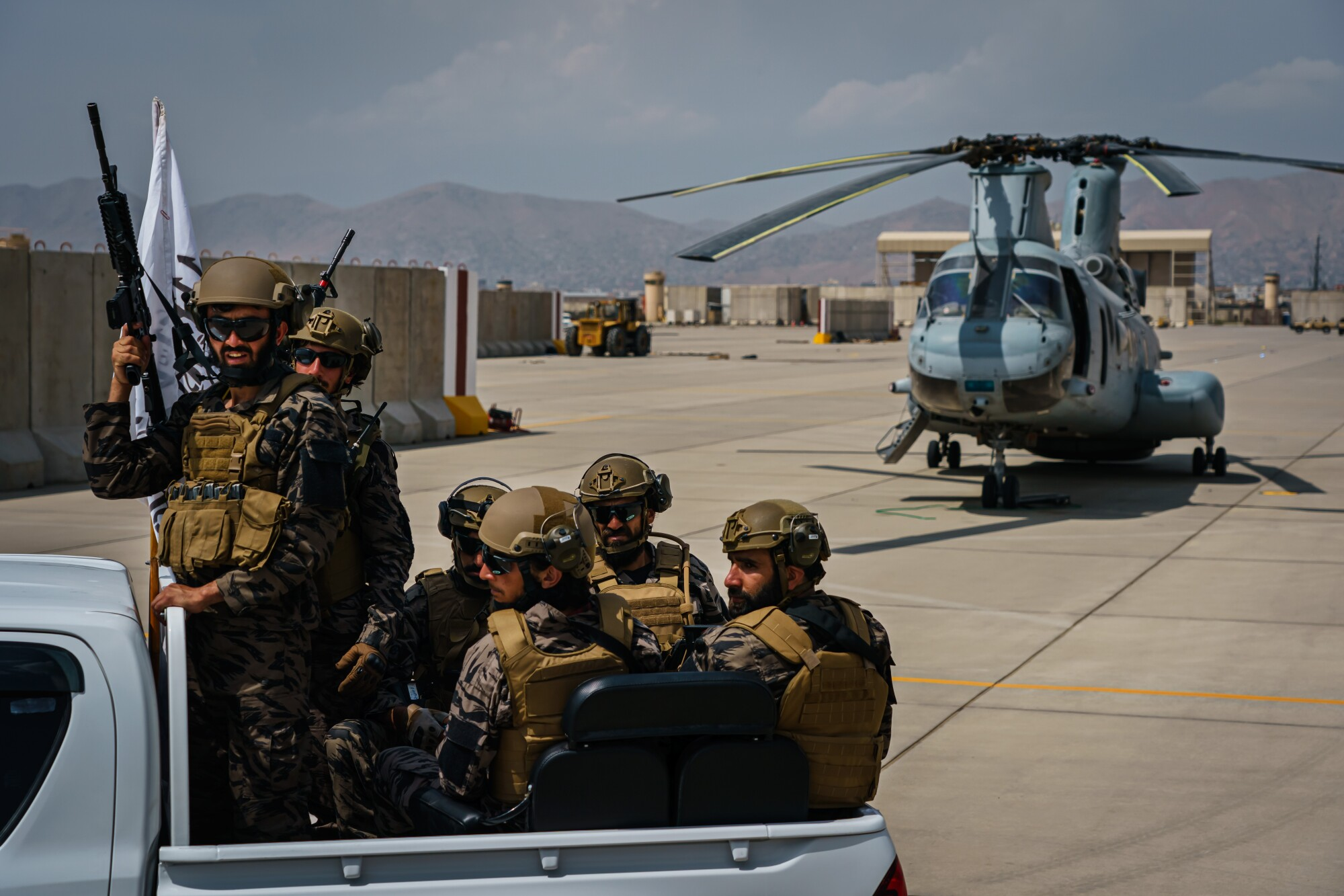 Armed Taliban fighters ride in a truck past a helicopter left at Hamid Karzai International Airport in Kabul