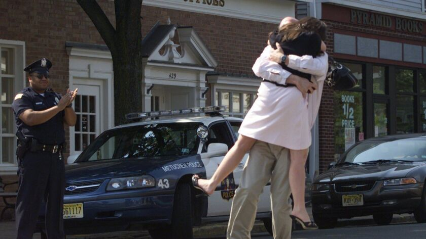 A man sweeps his future bride off her feet after she accepted his proposal in the middle of Main Street in Metuchen, N.J., on on May 9, 2004.