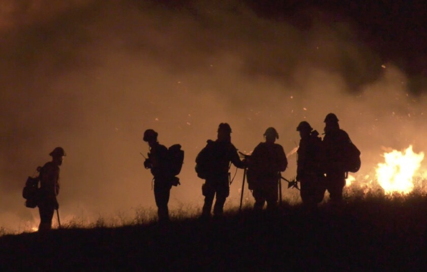 Firefighters are seen in silhouette on a hillside, with smoke and flames in the background.