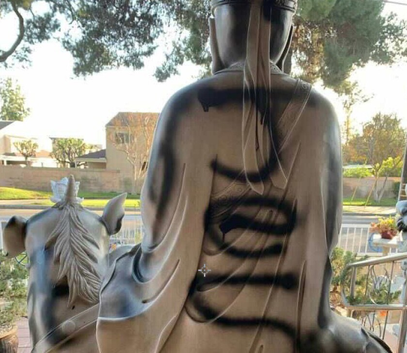 "Black spray paint including the word ""Jesus"" on a Buddhist statue"