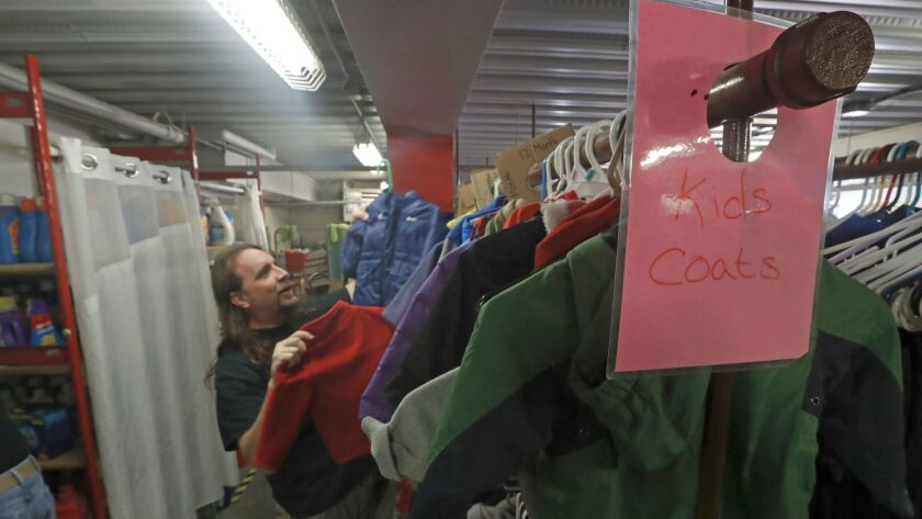 Brent Dalton, day shift supervisor at the Road Home shelter, hangs up donated children's coats in the warehouse.