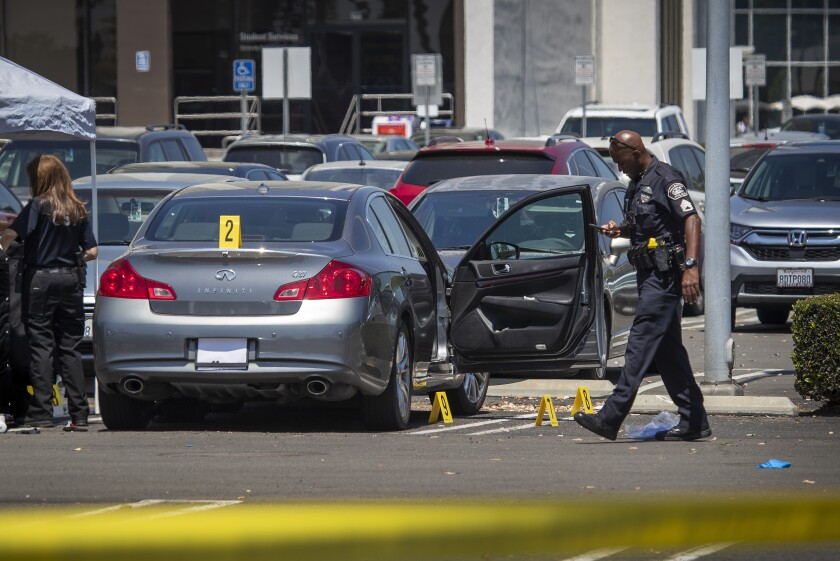 Evidence markers are placed around a vehicle Monday following the fatal stabbing at Cal State Fullerton.