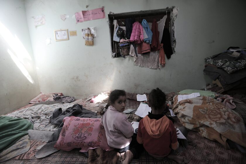 Cousins of Yassin and Isra Abu Khoussa inspect their destroyed room in Beit Lahiya in the northern Gaza Strip on Saturday.