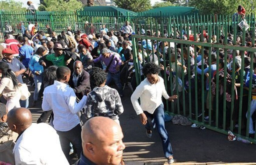Thousands of young students and their parents push their way into the gates causing a stampede at the University of Johannesburg, South Africa, Tuesday Jan. 10, 2012. Prospective students stampeded at the gate of a university Tuesday, leaving one person dead and two others seriously injured, officials said. (AP Photo/Adrian de Kock)
