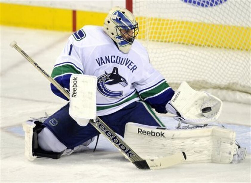Vancouver Canucks goalie Roberto Luongo makes a save during against the Calgary Flames during the second period of an NHL hockey game in Calgary, Alberta, Wednesday, April 10, 2013. (AP Photo/The Canadian Press, Larry MacDougal)