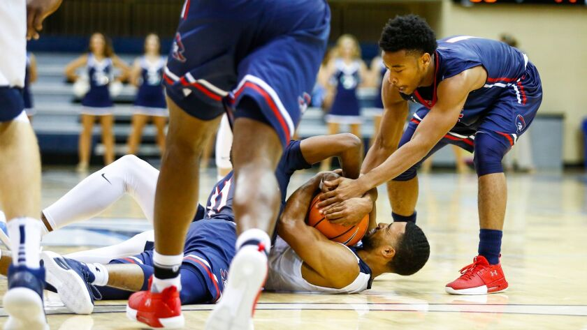 USD's Isaiah Wright fights for control of a loose ball with Robert Morris' Dachon Burke and Jon Williams.