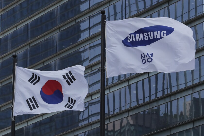 A Samsung Group flag and South Korean national flag flutter on adjacent poles outside office building