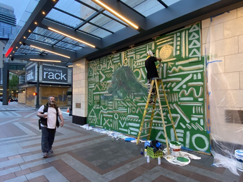 Procter nears completion of a mural on Nordstrom in downtown Seattle as a man walks by.