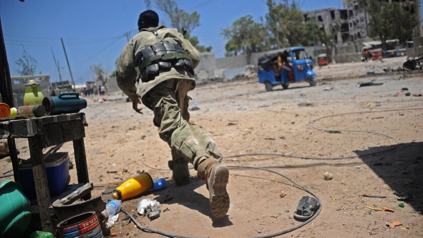 A Somali soldier runs for cover at the scene of two explosions near the ministries of public works and labor in Mogadishu.