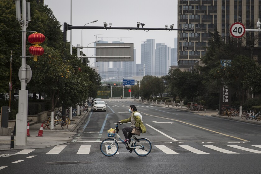 A bicyclist rides through the deserted streets of Wuhan, China, in February.