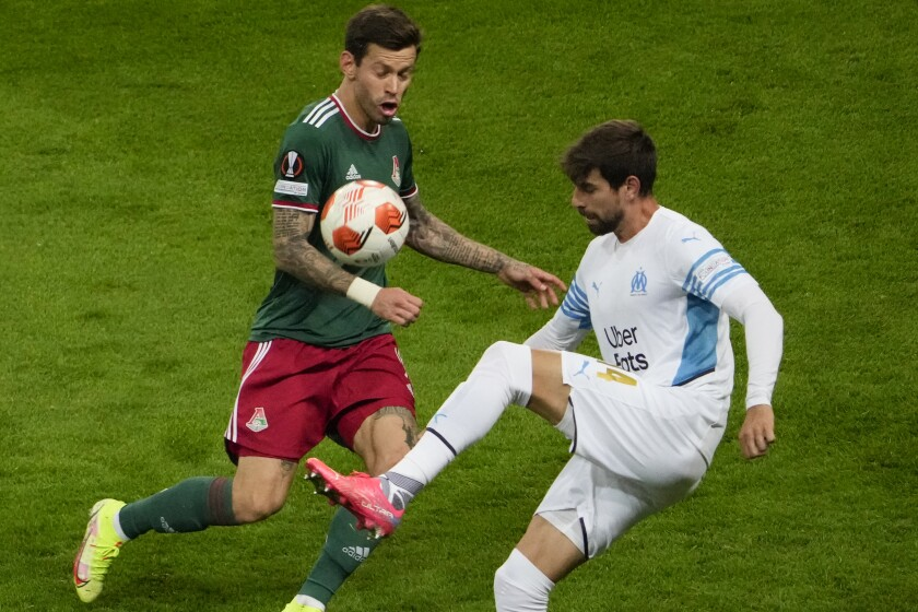 Marseille's Luan Peres, right, and Lokomotiv's Fedor Smolov challenge for the ball during the Europa League Group E soccer match between Lokomotiv Moscow and Marseille at the Lokomotiv stadium in Moscow, Russia, Thursday, Sept. 16, 2021. (AP Photo/Pavel Golovkin)