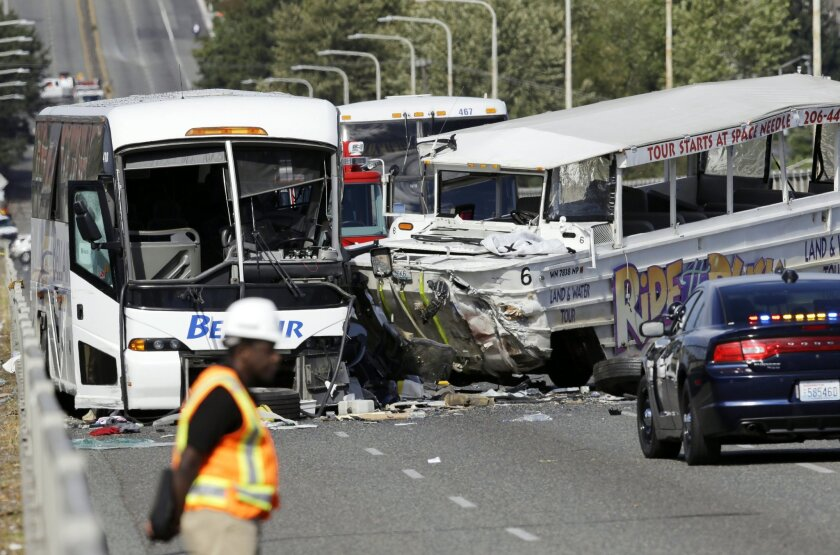"""An emergency official stands near a charter bus, left, and a """"Ride the Ducks"""" amphibious tour bus following a fatal crash that killed five people Thursday, Sept. 24, 2015, in Seattle. The duck boat did not have an axle repair that was recommended for at least some of the amphibious tour vehicles in 2013, federal investigators said.(AP Photo/Ted S. Warren)"""