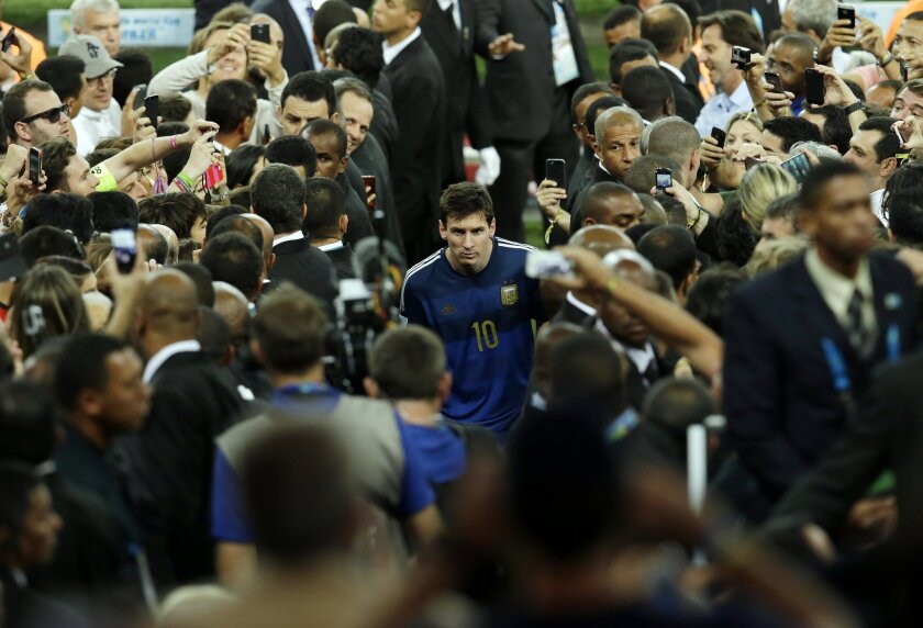 Argentina's Lionel Messi walks up the tribune to collect the second place trophy after the World Cup final soccer match between Germany and Argentina at the Maracana Stadium in Rio de Janeiro, Brazil, Sunday, July 13, 2014. Germany won 1-0. Germany won 1-0.(AP Photo/Hassan Ammar)