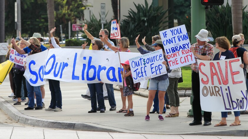 People opposing the plan to outsource library services hold up signs and wave to traffic outside Escondido City Hall before a council meeting August