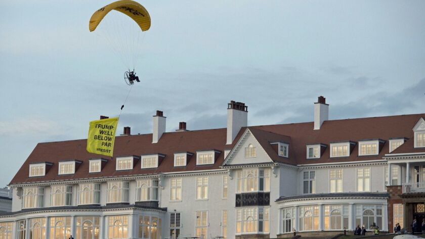 In this Friday, July 13, 2018 photo, a Greenpeace protester flying a microlight passes over US Presi