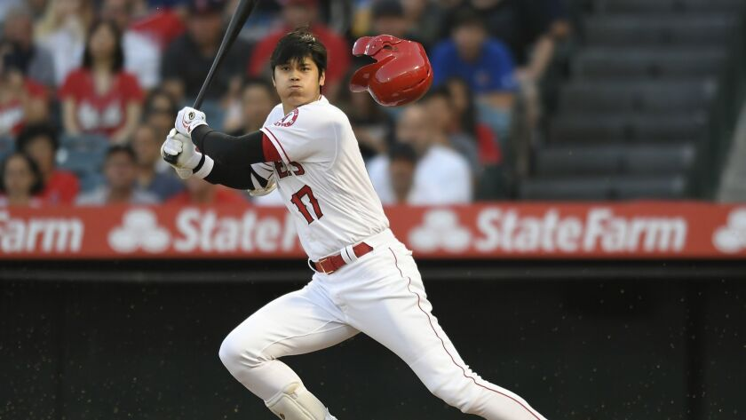 Angels designated hitter Shohei Ohtani loses his helmet while swinging at a pitch during the first inning of a 9-6 victory over the Houston Astros on Monday.