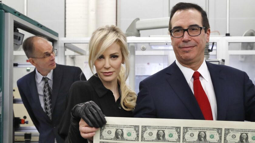Sheets of greenbacks don't equal economic growth: Treasury Secretary Steven T, Mnuchin, right, and his wife Louise Linton hold a sheet of new $1 bills, the first currency notes bearing his signature, at the Washington mint in November 2017.