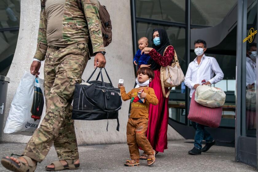 بزرگسالان که چمدان های کوچک حمل می کنند با کودکان پیاده روی می کنند