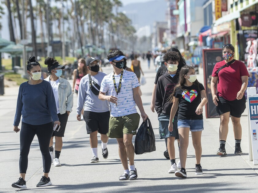 People wear masks to protect against the coronavirus while walking May 14 along the boardwalk in Venice Beach.