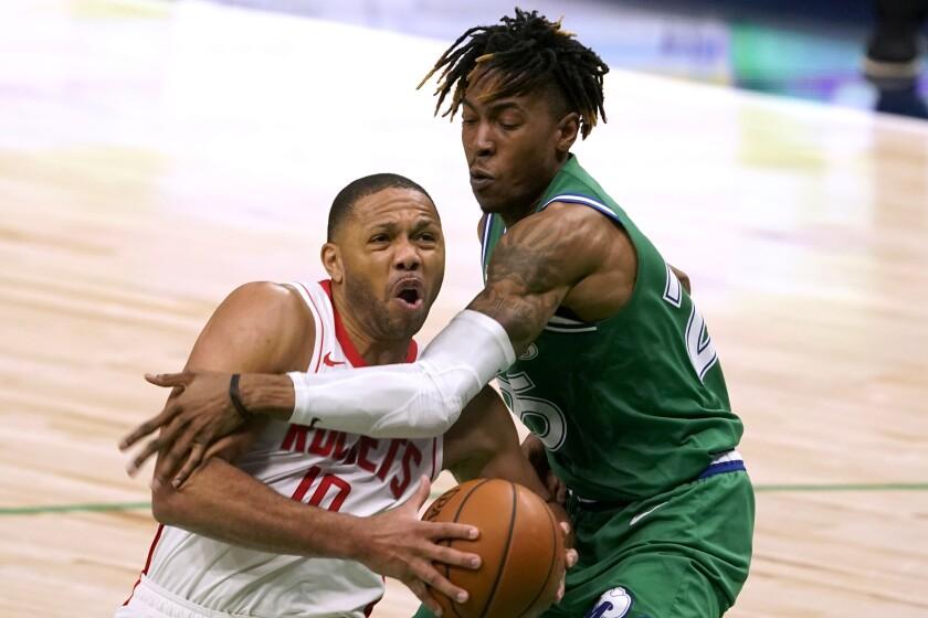 Eric Gordon, base de los Rockets de Houston, trata de eludir a Wes Iwundu, de los Mavericks de Dallas,
