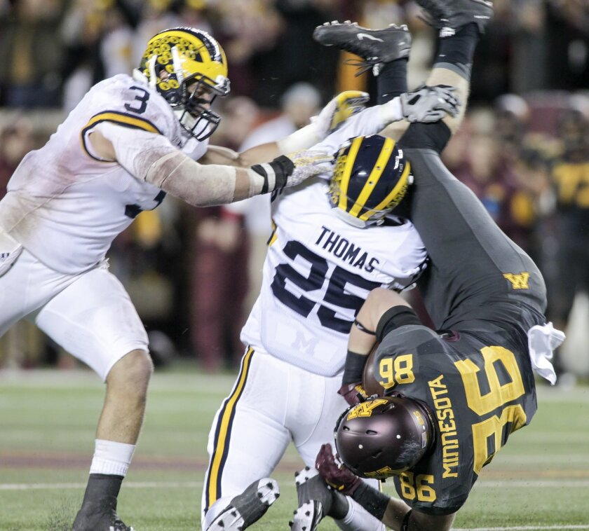 Minnesota tight end Brandon Lingen (86) is upended by Michigan's Dymonte Thomas (25) and Desmond Morgan (3) after a 23 yard catch during the second half of an NCAA college football game Saturday, Oct. 31, 2015, in Minneapolis.(AP Photo/Paul Battaglia)